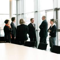 Sechs Mitarbeiter eines Unternehmens stehen im Besprechungsraum vor einem Fenster und unterhalten sich.
